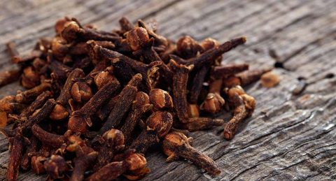 Whole Cloves on Wooden Table